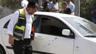 Anschlag in Jerusalem: Ein Polizeioffizier untersucht das von Projektilen durchsiebte Auto des palästinensischen Angreifers, der bei einem Feuergefecht getötet wurde.