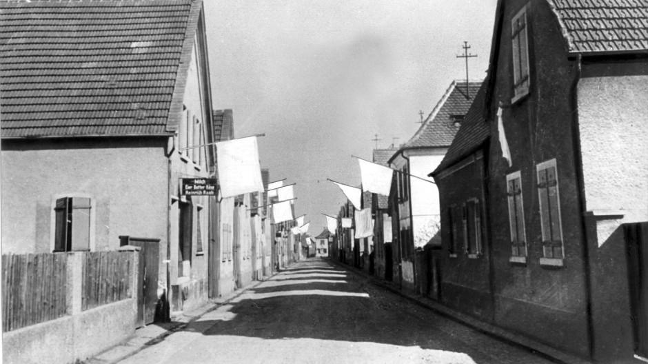Die Bewohner eines Dorfes in der Pfalz haben zum Zeichen der Kapitulation weiße Fahnen aus den Fenstern ihrer Häuser gehängt.
