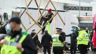 Ein Demonstrant klettert in Broxbourne von einer Bambuskonstruktion, die als Blockade vor einer Druckerei genutzt wurde.