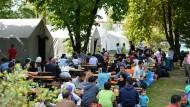 Flüchtlinge sitzen am 13. September 2015 kurz nach ihrer Ankunft in einem Zeltlager an der Donnersberger Brücke in der Nähe des Hauptbahnhofs in München.