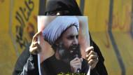 Eine weibliche Demonstrantin hält ein Banner des hingerichteten schiitischen Geistlichen Nimr Baker al Nimr in der Hand. Er war ein entschiedener Gegner des erzkonservativen sunnitischen Königshauses in Riad.