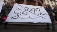 Mit einem Transparent fordern Demonstrantinnen vor dem Amtsgericht Gießen die Abschaffung des Paragrafen 219a (Archivbild).
