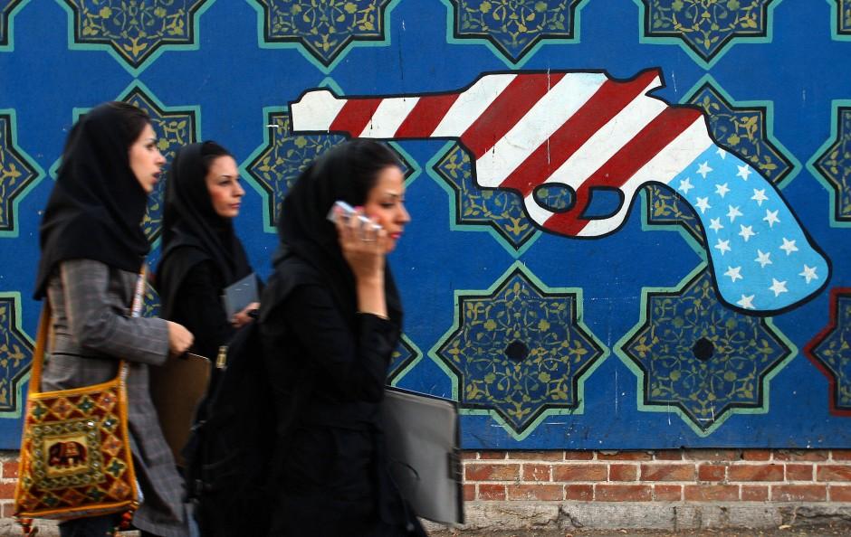 Der lange amerikanische Arm: Studentinnen in Teheran, im Hintergrund antiamerikanische Wandmalerei