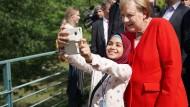 Bundeskanzlerin Merkel macht während des Tages der offenen Tür der Bundesregierung am 18. August mit einem jungen Mädchen ein Selfie.