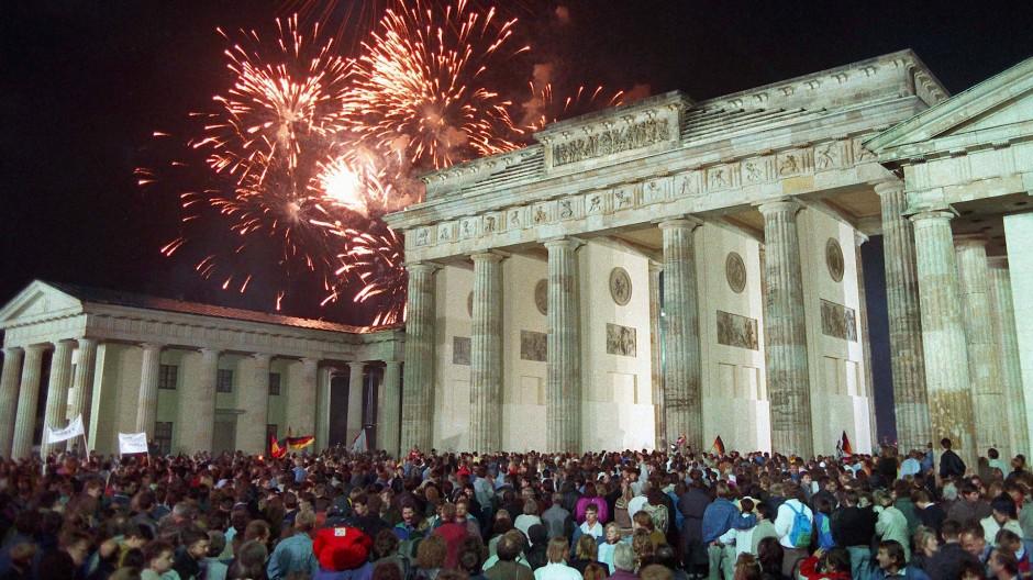 Mit einem Feuerwerk am Brandenburger Tor feiern die Berliner am 3. Oktober 1990 die Wiedervereinigung