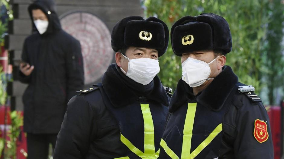 Sicherheitsbeamte tragen in einem Einkaufsviertel in Peking bei ihrer Arbeit Atemschutzmasken.
