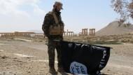 Ein Mitglied regierungstreuer Truppen trägt vor der Stadt Palmyra eine IS-Flagge.