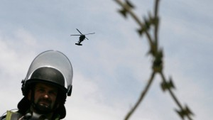 A helicopter flies over a Hungarian KFOR soldier blocking the road near the Mitrovica during clashes in the town of Zvecan