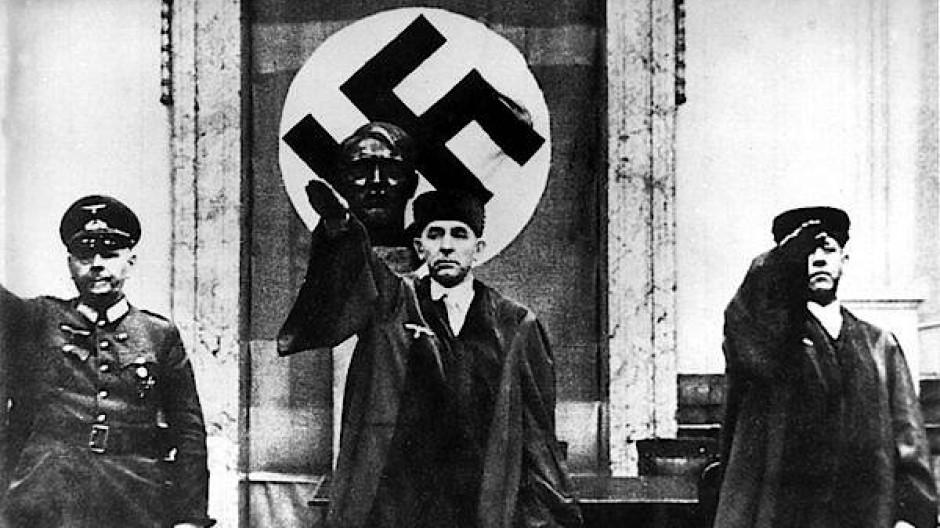 Roland Freisler (Mitte) im Gerichtssaal mit Hitlergruss