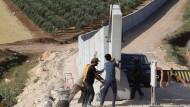Eine Mauer für mehr Ruhe: Arbeiter befestigen einen Abschnitt der türkisch-syrischen Grenze in der Provinz Hatay, doch der Grenzverkehr der Dschihadisten geht weiter