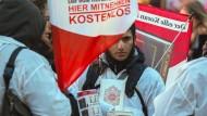 """Mit einem Plakat auf dem Rücken versuchte ein Teilnehmer der Koran-Verteilaktion """"Lies!""""» am 31 Januar 2015 auf der Zeil in Frankfurt am Main die Aufmerksamkeit auf sich zu ziehen."""