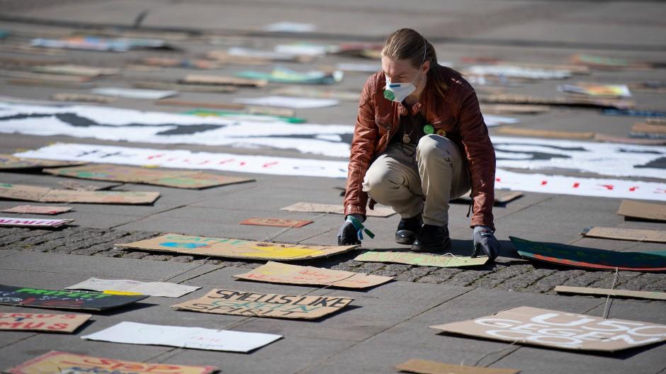 Sehnsucht nach Protest: Ein Aktivist von Fridays for Future legt Schilder und Plakate während einer Aktion auf dem Rathausmarkt in Hamburg aus.