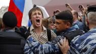 Greiftrupps im Einsatz: Die Polizei blockiert im Stadtzentrum Moskaus einen schreienden Demonstranten.