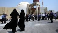 Weibliche Sicherheitskräfte vor dem iranischen Atomkraftwerk Buschehr beobachten Medienvertreter.