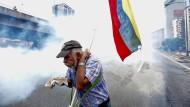Ein Demonstrant versucht sich vor dem Tränengas zu schützen. In Caracas setzten die Sicherheitskräfte das Gas massiv gegen die Protestierenden ein.