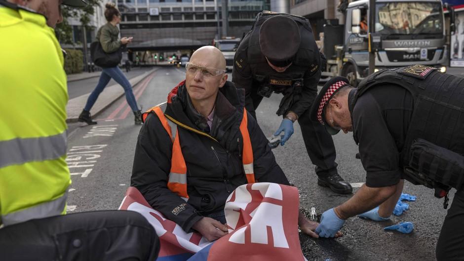 """Ein Aktivist von """"Insulate Britain"""" hat sich am Montag auf eine Straße in London geklebt."""