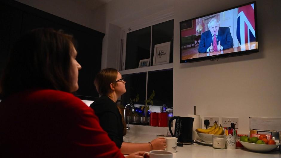 Eine Familie aus Liverpool sieht sich die Ansprache von Premierminister Boris Johnson im Fernsehen an.