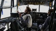 Taliban-Kämpfer sitzen im Cockpit eines Flugzeugs der afghanischen Armee, das diese am Flughafen Kabul zurückgelassenen hatte. Das Pentagon teilte mit, dass die amerikanischen Soldaten militärisches Gerät vor ihrem Abzug unbrauchbar gemacht habe.