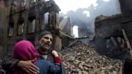 Eine kaschmirische Frau tröstet einen Verwandten, nachdem sein Haus in Kaschmir zerstört wurde.