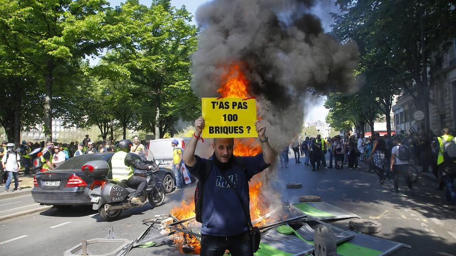 """""""Du hast keine 100 Steine?"""", fragt ein Teilnehmer der Gelbwesten-Proteste vor einer Polizeisperre. Die Bewegung will die Regierung daran erinnern, dass das Geld an wichtigeren Stellen als dem Wiederaufbau von Notre Dame gebraucht werde."""