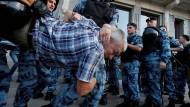 Polizisten nehmen am Samstag einen Demonstranten in Moskau fest.