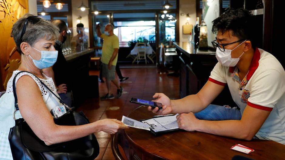 Ein Mitarbeiter einer Pizzeria in Rom kontrolliert einen Impfpass.