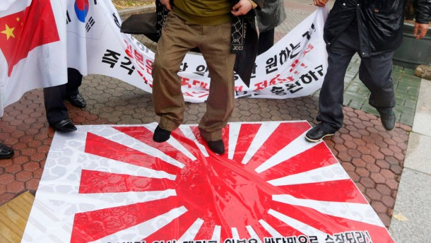 South Korean members of anti-Japan civic group step on Japanese rising sun flag during protest in Seoul