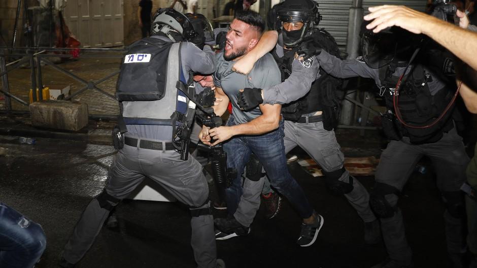 Polizisten nehmen einen Demonstranten nahe dem Damaskustor in Gewahrsam.