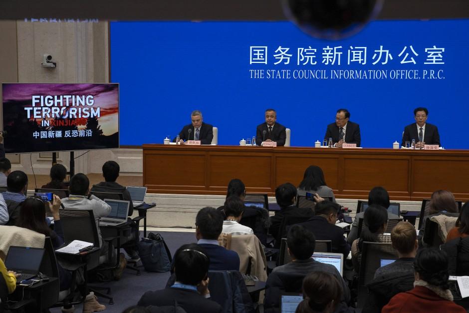 Auf einer Pressekonferenz in Peking zeigt der Gouverneur von Xinjiang, Shohrat Zakir (Zweiter von rechts) am Montag einen Film über Terrorismus in der Provinz.