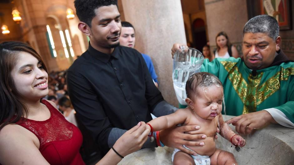 Es werden immer mehr: Pfarrer Moises Villalta tauft die kleine Madilynn in der Herz-Jesu-Kirche im Norden Washingtons.