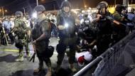 Von Demonstranten umschlossen: Schwer bewaffnete Polizisten in Ferguson am Mittwochmorgen