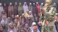 In dem von Boko Haram verbreiteten Video ist ein maskierter Mann zu sehen, der von Mädchen umgeben ist, die einige der entführten Schülerinnen aus Chibok sein sollen.