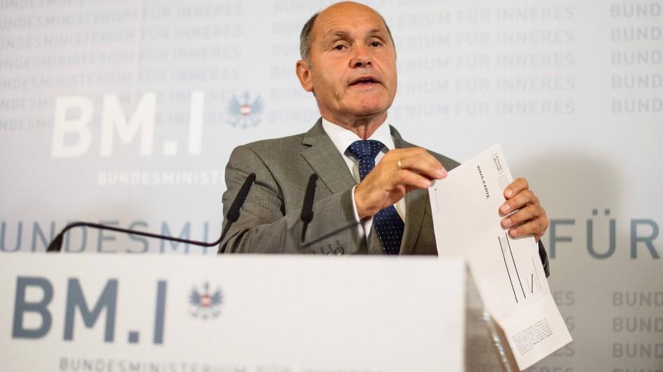 Österreichs Innenminister Sobotka mit einer Wahlkarte, die für die Verschiebung des Wahltermins verantwortlich waren.