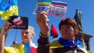 Anti-Putin-Demonstranten fordern vor dem EU-Sondergipfel in Brüssel ein härteres Vorgehen gegen den russischen Präsidenten