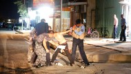 Am Straßenrand halten zwei Polizisten den Jungen fest, während weitere Sicherheitskräfte die Weste von seinem Körper entfernen.