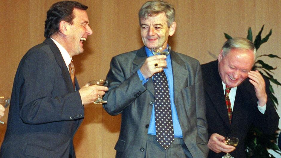 In Champagnerlaune: Gerhard Schröder, Joschka Fischer und Oskar Lafontaine (v.l.n.r.) nach der Unterzeichnung des rot-grünen Koalitionsvertrags am 20. Oktober 1998 in der NRW-Landesvertretung in Bonn