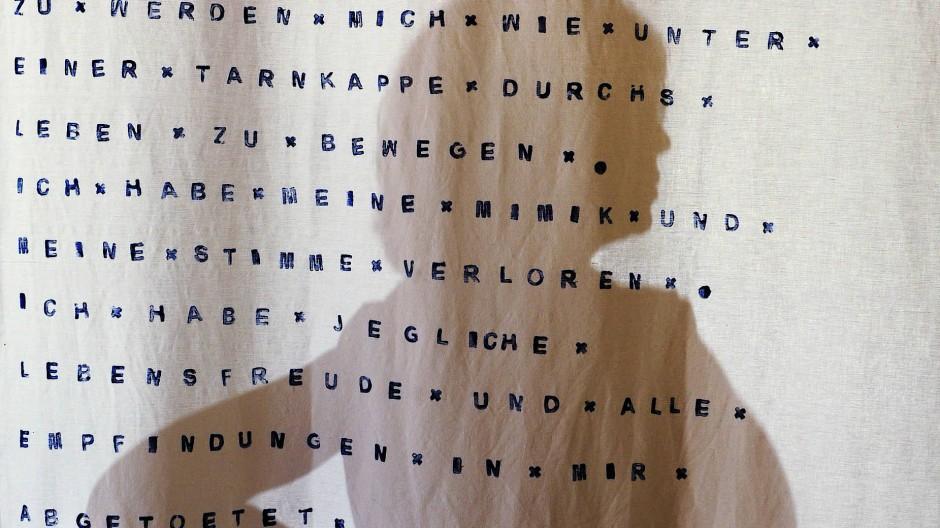 Die Künstlerin Anna von der Heiden, ehemalige Schülerin der Odenwaldschule und selbst Missbrauchsopfer, steht hinter einer von ihr bedruckten Stoffbahn, die sexuellen Missbrauch thematisiert.
