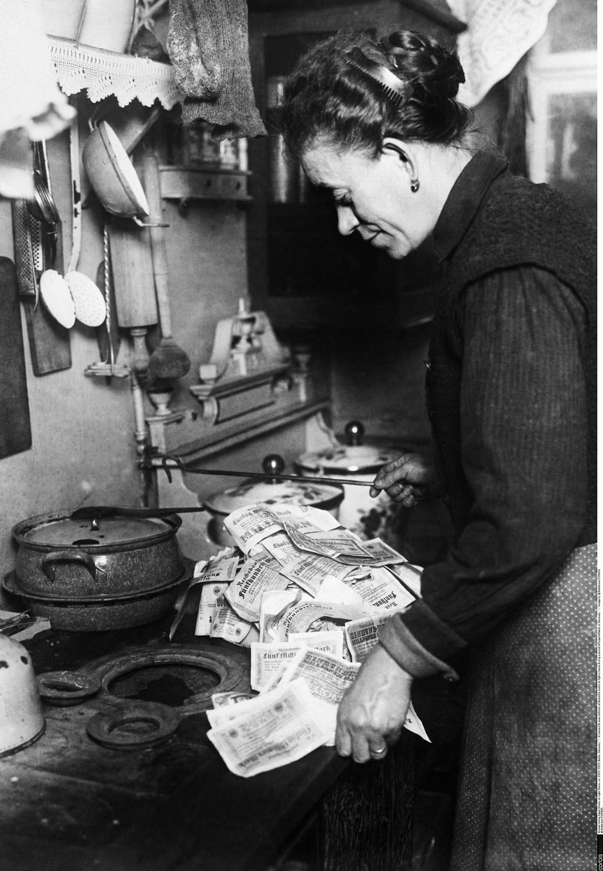 Nicht viel wert: Eine Deutsche nutzt während der Hyperinflation Anfang der 1920er Jahre Geld als Brennmittel für den Herd.