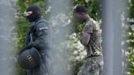 Nach den Ausschreitungen in einer Landeserstaufnahmeeinrichtung für Flüchtlinge wird ein Mann von einem maskierten Polizisten eskortiert