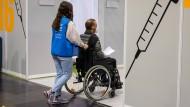 Bei einem Probelauf im Impfzentrum im Berliner Velodrom schiebt eine Helferin einen Patienten im Rollstuhl.