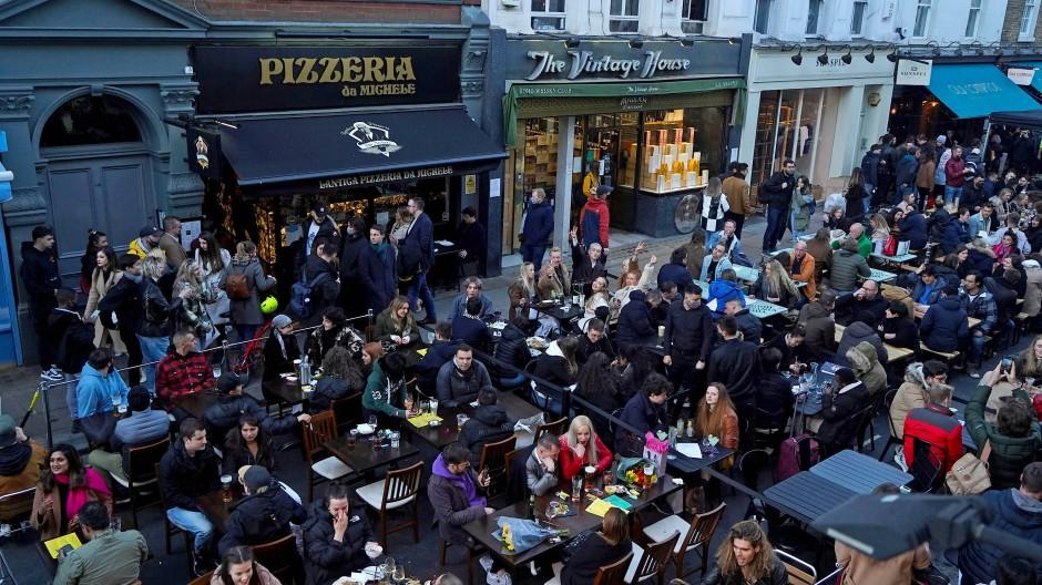 Menschen sitzen am 16. April in einer Straße im Londoner Stadtteil Soho an Restauranttischen.