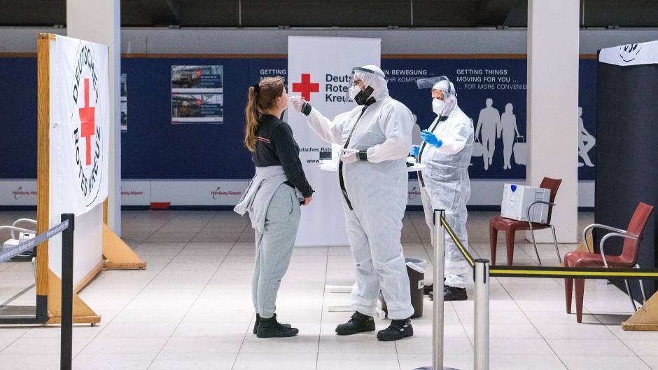 Hamburg: Eine Reisende lässt am Flughafen von einem Mitarbeiter des Deutschen Roten Kreuzes (DRK) einen Corona-Test machen.