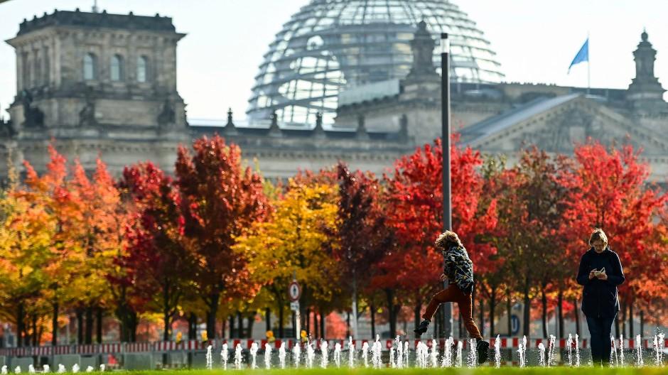Ein Kind springt vor dem Bundestag in Berlin am 19. Oktober über Wasser-Fontänen.