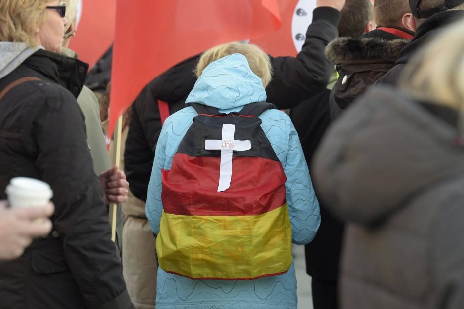 Ein aussagekräftiger Rucksack bei den Anti-Merkel-Protesten: Schwarz-Rot-Gold wird zu Grabe getragen.
