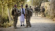 Ein Bundeswehrsoldat (links) und ein Dolmetscher (rechts) sprechen nahe Kundus im Distrikt von Char Darreh im August 2011 mit einem Mann.
