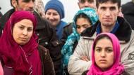 Männer und Frauen auf Afghanistan und Pakistan warten im Februar in einer Flüchtlingsunterkunft in Hessen auf die Essensausgabe
