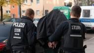 Polizeibeamte führen einen festgenommenen Mann nach einer Razzia in Berlin in Handschellen ab (Symbolbild).