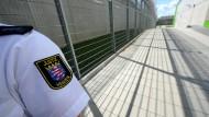 Ein Justizbeamter steht im August 2011 an den Sicherheitszäunen der Justizvollzugsanstalt Frankfurt (Symbolbild).