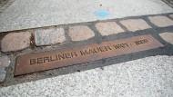 Ein Schild erinnert an den ehemaligen Verlauf der Berliner Mauer.