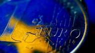 Die Fahne der EU spiegelt sich in einer Euro-Münze